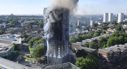 LONDON, ENGLAND - JUNE 14: Smoke rises from the building after a huge fire engulfed the 24 storey residential Grenfell Tower block in Latimer Road, West London in the early hours of this morning on June 14, 2017 in London, England. The Mayor of London, Sadiq Khan, has declared the fire a major incident as more than 200 firefighters are still tackling the blaze while at least 50 people are receiving hospital treatment. (Photo by Leon Neal/Getty Images)